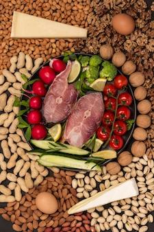 Poisson de rivière, tomates cerises, concombres, citron, brocoli, romarin en plaque noire. fromage et noix sur table. mise à plat