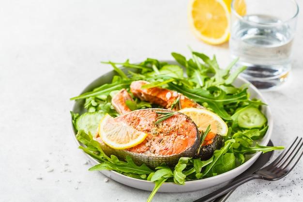 Poisson rouge frit avec salade de roquette et concombre dans une assiette blanche, espace de copie.