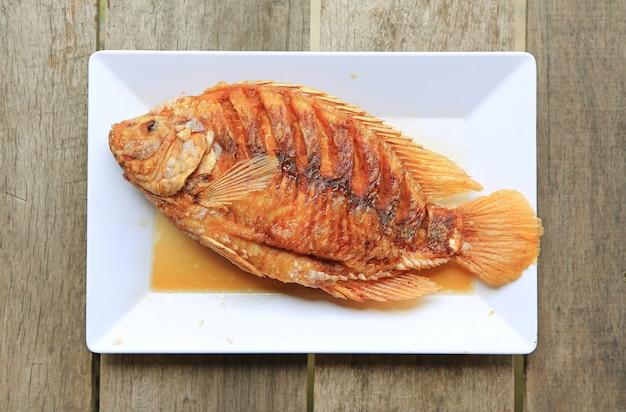 Poisson ruby frit sur une assiette carrée blanche contre une table en bois - menu de plats thaïlandais réputés