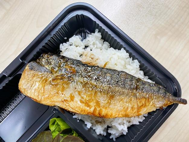 Poisson saba grillé avec sauce teriyaki sur bol de riz garni dans le récipient en plastique