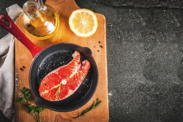 Poisson saumon frais cru avec des ingrédients pour la cuisson - huile d'olive, citron, oignon, persil, romarin
