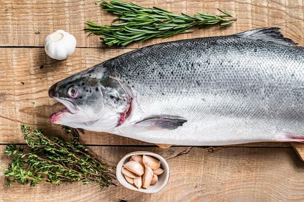 Poisson saumon marin cru sur une table de cuisine en bois avec des herbes
