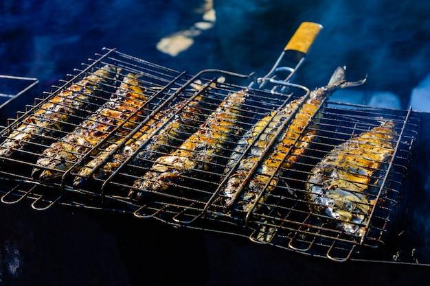 Poisson scomber entier cuit dans un grill à grille métallique
