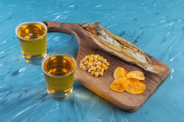 Poisson séché, chips, pois chiches sur une planche à découper à côté d'un verre de bière, sur la surface bleue.