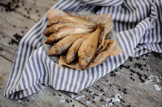 Poisson séché à la fumée aromatisé sur plaque sur un papier sulfurisé sur la serviette à rayures grises sur la table en bois