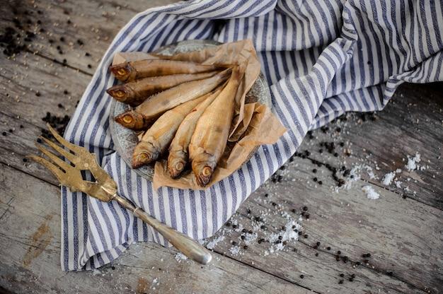 Poisson séché à la fumée sur une assiette sur un papier sulfurisé sur la serviette à rayures grises avec une fourchette dorée décorée sur la table en bois.