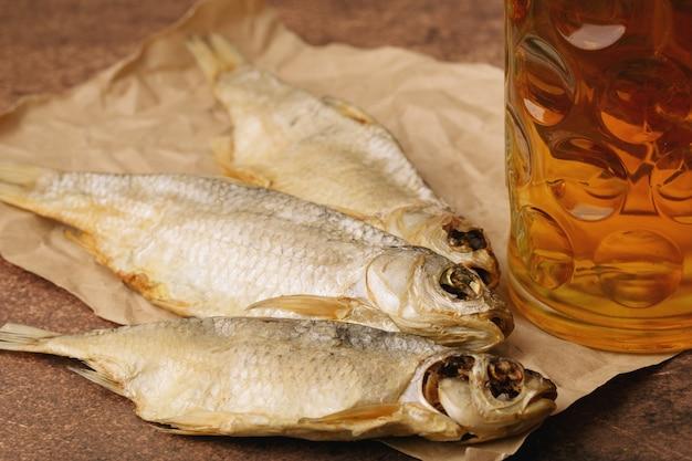 Poisson séché en gros plan, verre de bière sur un fond de papier et marron. format horizontal