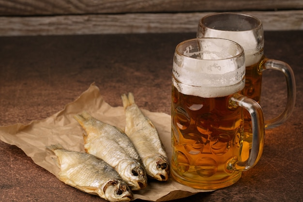Poisson séché en gros plan, verre de bière vintage sur un fond en bois sombre. format horizontal