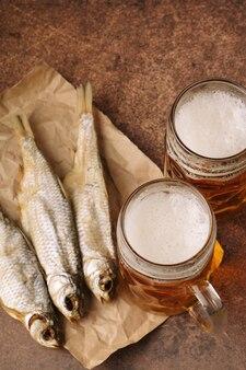 Poisson séché en gros plan, verre de bière vintage sur un fond en bois sombre. vue de dessus. format vertical