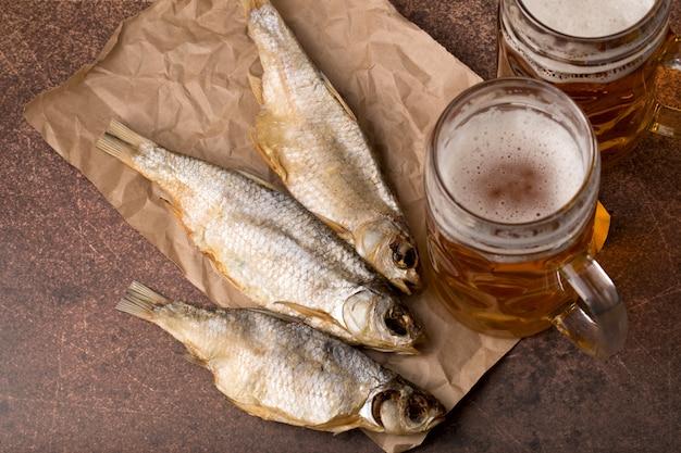 Poisson séché en gros plan, verre de bière vintage sur un fond en bois sombre. vue de dessus. orientation horizontale.