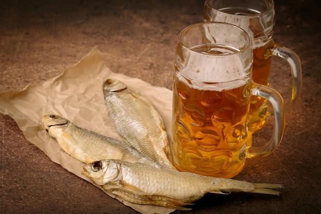 Poisson séché en gros plan, verre de bière vintage sur fond de papier et marron. format horizontal