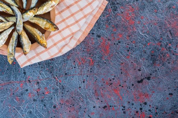 Poisson séché salé isolé sur une plaque d'argile sur un fond sombre.