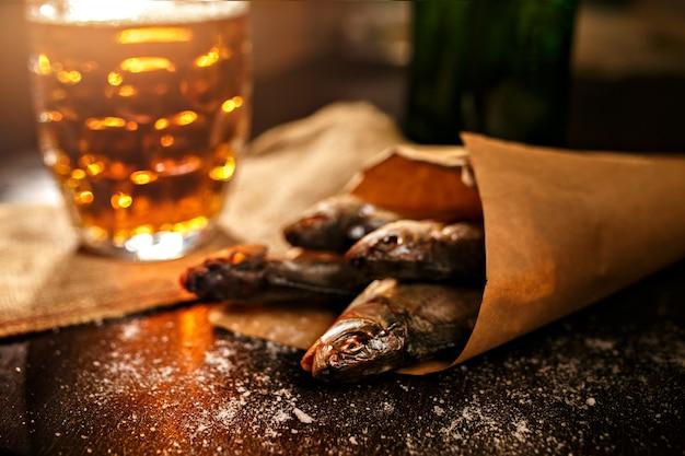 Poisson séché et verre de bière vintage sur une surface noire