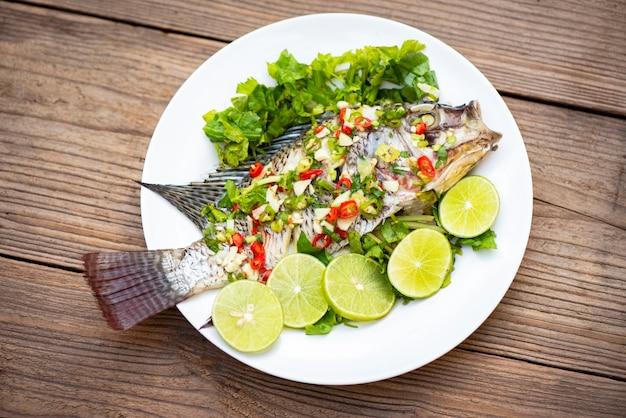 Poisson tilapia cuit à la vapeur avec sauce chili et citron vert aux herbes et légumes sur assiette, citron vert à la vapeur de poisson - cuisine thaïlandaise
