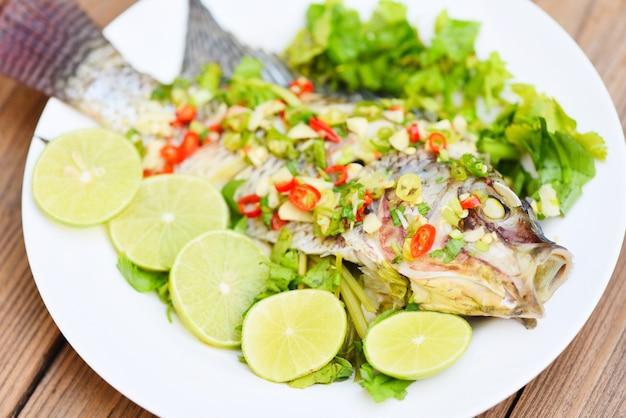 Poisson tilapia cuit à la vapeur avec sauce chili et citron vert aux herbes et légumes sur assiette, nourriture cuite à la vapeur de poisson tilapia citron vert - cuisine thaïlandaise