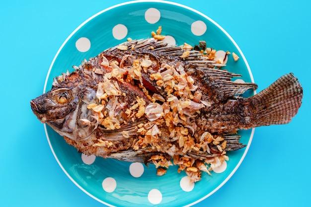 Poisson tilapia frit dans une assiette à pois sur fond bleu