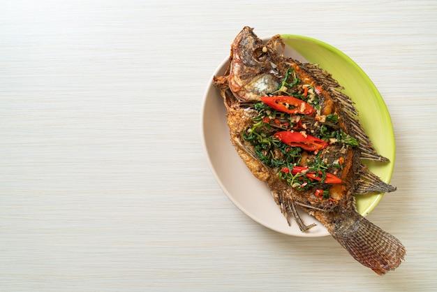 Poisson tilapia frit avec sauce à l'ail et chili basilic sur le dessus - style de cuisine maison