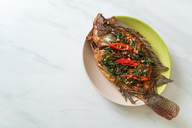 Poisson tilapia frit avec sauce à l'ail et chili basilic sur le dessus