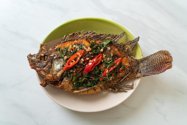 Poisson tilapia frit avec sauce au basilic et à l'ail chili sur le dessus