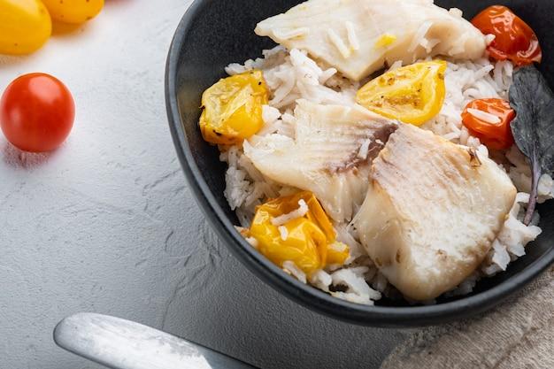 Poisson tilapia avec riz basmati et tomates cerises, dans un bol, sur fond blanc