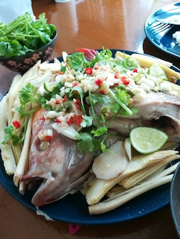 Poisson tilapia rouge cuit à la vapeur avec sauce chili citron vert poisson citron vert thaï poisson cuit à la vapeur dans une vinaigrette au citron vert