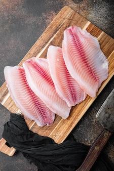 Poisson tilapia, viande sans peau, sur une vieille table rustique, vue de dessus