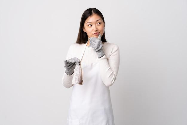 Poissonnier chinois portant un tablier et tenant un poisson cru sur blanc pensant à une idée tout en regardant