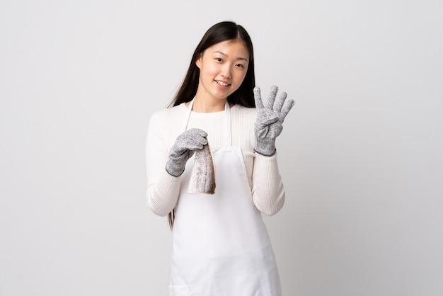 Poissonnier chinois portant un tablier et tenant un poisson cru sur un mur blanc isolé heureux et comptant quatre avec les doigts