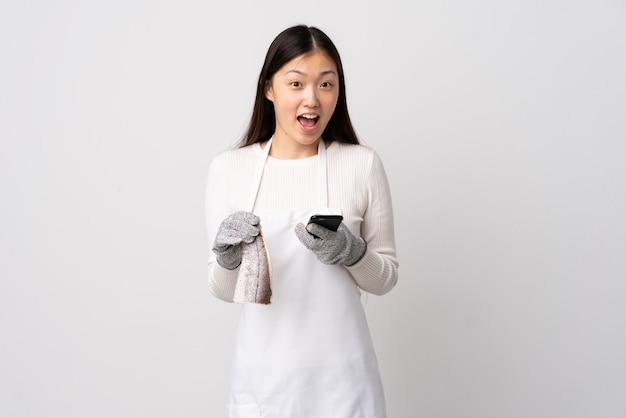 Poissonnier chinois portant un tablier et tenant un poisson cru sur un mur blanc isolé surpris et envoyant un message