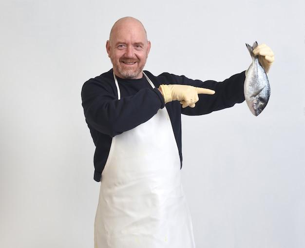 Un poissonnier tenant et pointant du doigt une dorade