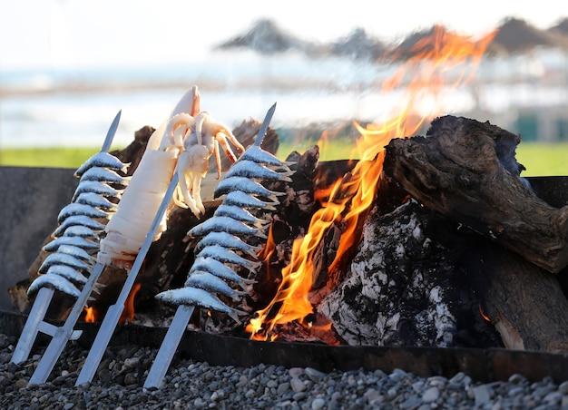 Poissons assortis en brochettes de bûches et feu avec plage et parasols