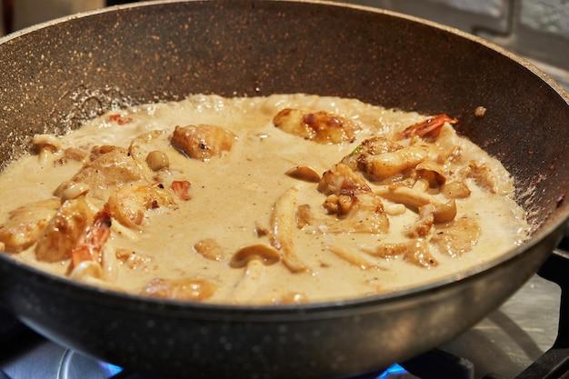 Les poissons aux champignons et crevettes sont frits dans de l'huile dans une poêle en sauce, recette pas à pas sur internet.
