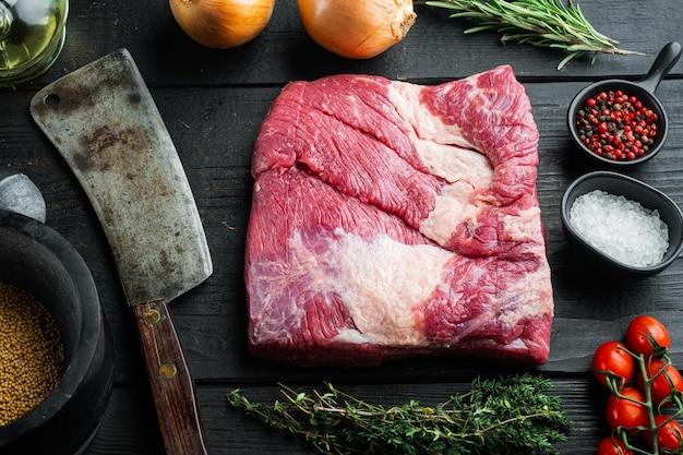 Poitrine de poitrine coupée à plat, ensemble de viande de poitrine de boeuf crue, avec des ingrédients pour fumer le barbecue, pastrami, cure, sur fond de table en bois noir