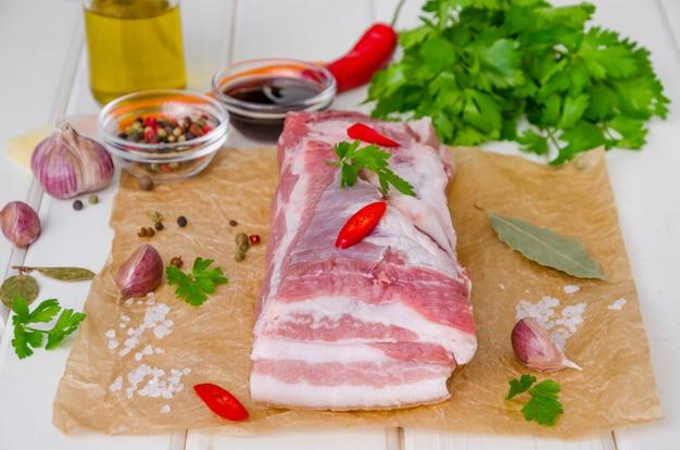 Poitrine de porc fraîche crue avec sel, poivre, ail, piment, sauce soja et miel sur un bois blanc