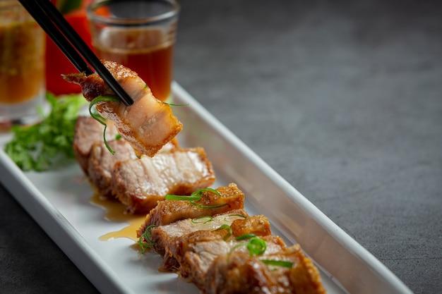 Poitrine de porc frite avec sauce de poisson sur fond sombre