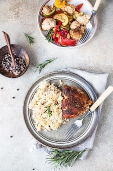 Poitrine de poulet au four avec du riz sur une assiette servie avec des légumes rôtis