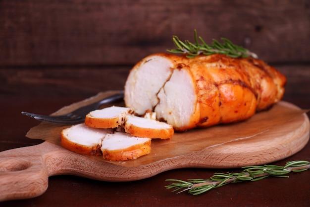 Poitrine de poulet au jambon cuite au romarin sur une planche à découper en bois