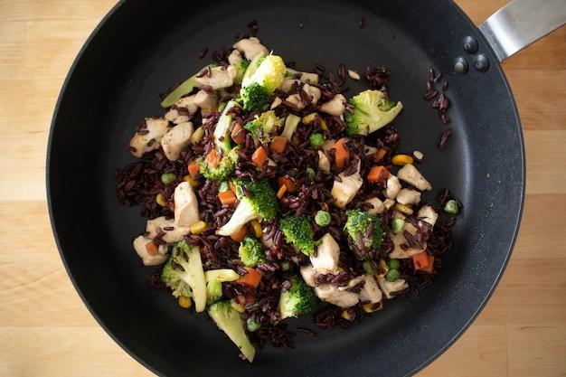 Poitrine de poulet en bonne santé au feu de riz noir sur une poêle chaude.