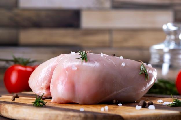 Poitrine de poulet cru sur une planche à découper avec des herbes et des tomates