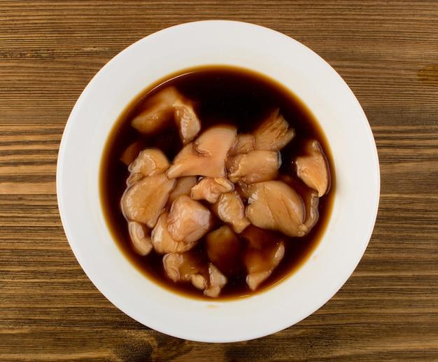 Poitrine de poulet crue marinée au soja. vue de dessus de morceaux de filet de dinde fraîche