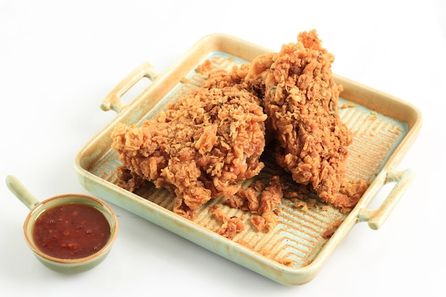 Poitrine de poulet frite croustillante dorée et ailes de poulet, servies sur une assiette carrée rustique avec sauce chili, isolée sur fond blanc avec espace de copie pour le texte