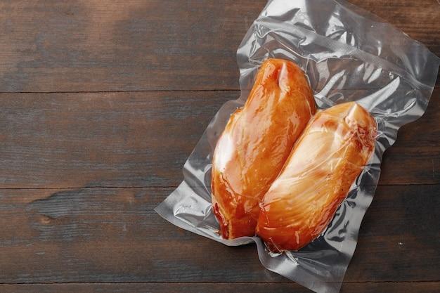 Poitrine de poulet fumée sur planche de bois brun