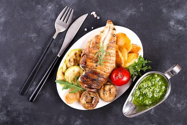 Poitrine de poulet grillade avec légumes et sauce pesto dans une poêle en fonte