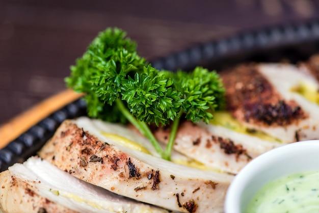 Poitrine de poulet grillé dans différentes variantes avec des tomates cerises, des haricots verts, de l'ail, des herbes, un citron coupé sur une planche de bois ou un pan en téflon. cuisine traditionnelle. cuisine grille.