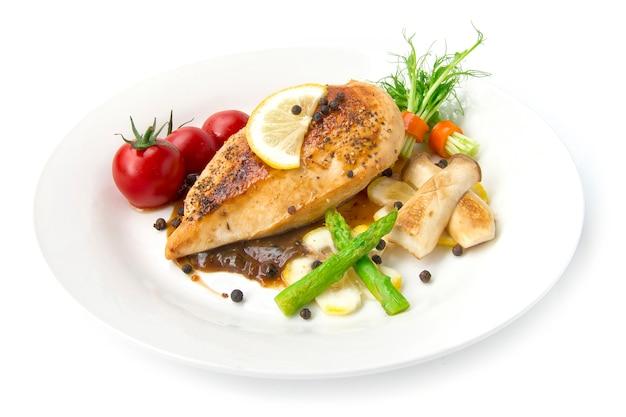 Poitrine de poulet grillé ou steak de poulet avec sauce aux poivrons noirs surmonté de poivrons noirs décorent les asperges, les pleurotes, la tomate et le citron vue de côté de style sculpté isolé sur fond blanc