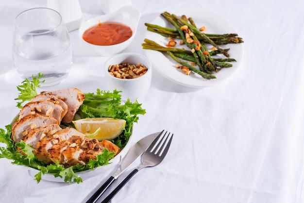 Poitrine de poulet grillée avec asperges grillées et tranche de citron. régime paléo. alimentation saine. concept pour un repas savoureux et sain.