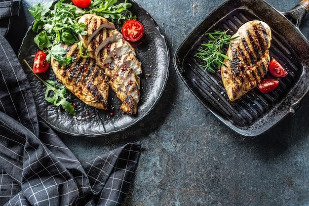 Poitrine de poulet grillée aux épices poivre sel tomates romarin et roquette - vue de dessus.
