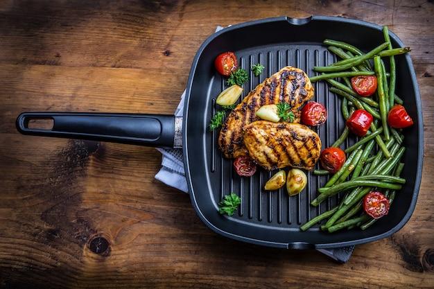 Poitrine de poulet grillée dans différentes variantes avec tomates cerises, haricots verts, herbes à l'ail citron coupé sur une planche de bois ou une poêle en téflon