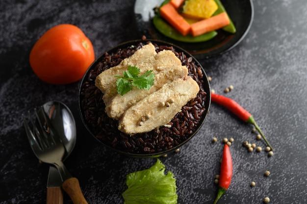 Poitrine de poulet grillée garnie de poivre sur des baies de riz pourpre mûre.