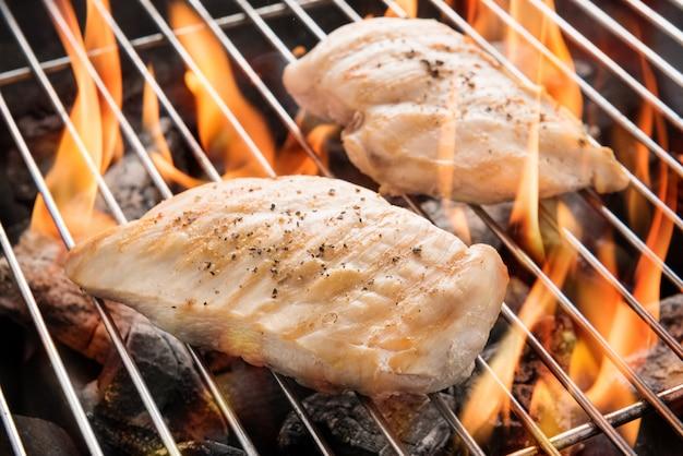 Poitrine de poulet grillée sur le gril enflammé